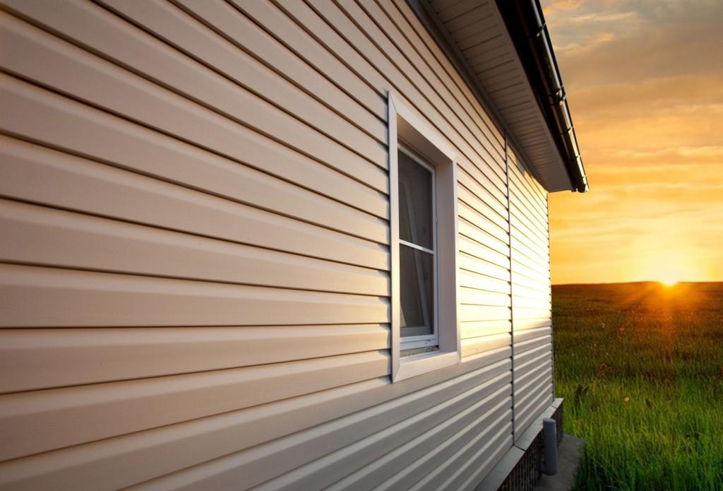 Фасад дома, отделанный металлической вагонкой. Материал, внешне напоминающий сайдинг, но отличающийся от него по способу крепления к основе