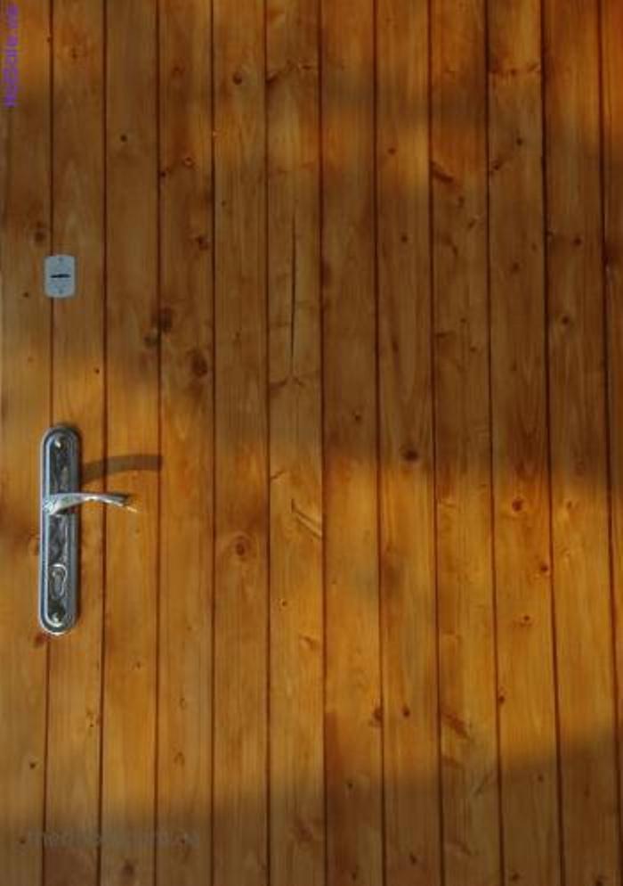 Металлическая дверь, обшитая вертикальной деревянной вагонкой