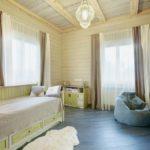 В спальне царят пастельные тона: фисташковый цвет прекрасно смотрится на фоне светлого дерева