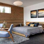 За основу этой спальни взяты белый и темно-серый цвет, но акцентная стена натурального древесного оттенка приводит интерьер в соответствие с мебелью и декором